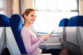 Young woman using her tablet computer while traveling by train — Foto de Stock