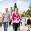 Two female tourists walking along the Charles Bridge while sight — Stock Photo
