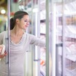 Young woman shopping for meat in a grocery store — Stock Photo #23475550