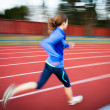 Young womrunning at track and field stadium — Stock Photo #23475628