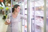 Junge frau für fleisch in einem lebensmittelladen einkaufen — Stockfoto