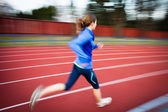 Young woman running at a track and field stadium — Stock Photo