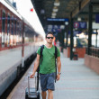 Just arrived: handsome young man walking along a platform at a m - Foto Stock