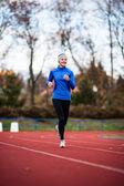 Jonge vrouw draait op een track & field stadion — Stockfoto