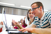 College-studenten sitzen in einem klassenzimmer mit einem laptopcomputer — Stockfoto