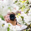 Pretty female photographer outdoors on a lovely spring day, taki - Stock Photo