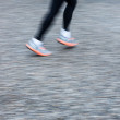 Motion blurred runner's feet in a city environment (panning tech - Stock Photo
