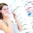 Pretty, young woman choosing new glasses frames in an optician s — Stock Photo
