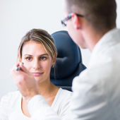 Optometry concept - pretty young woman having her eyes examined — ストック写真