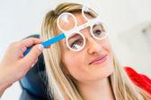 Optometrie konzept - hübsche junge frau, die ihre augen untersuchen — Stockfoto