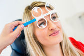 Optometry concept - pretty young woman having her eyes examined — Stok fotoğraf