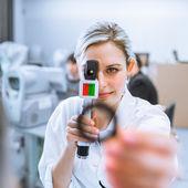 Concetto di optometria - optometrista piuttosto giovane al lavoro, examinatin — Foto Stock