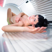 Pretty young woman tanning her skin in a modern solarium — Stock Photo
