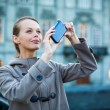 Elegant, young woman taking a photo with her cell phone camera — Stockfoto