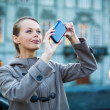 Elegant, young woman taking a photo with her cell phone camera — Stok fotoğraf