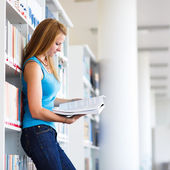 симпатичный молодой студент колледжа в библиотеке — Стоковое фото