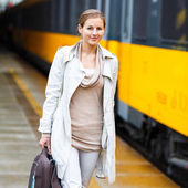 Pretty young woman at a train station (color toned image) — Stock Photo