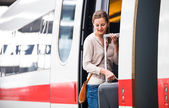 Pretty young woman boarding a train — Stock Photo