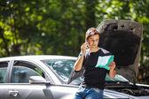 Que jovem bonito contactar a assistência técnica com seu carro quebrado — Fotografia Stock