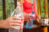 Woman fillig a plastic bottle — Stock Photo
