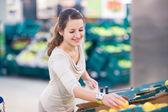 Mujer de compras en una tienda de abarrotes — Foto de Stock