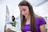 Vrouwelijke student op zoek naar boeken — Stockfoto