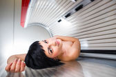 Woman tanning her skin in solarium — Stock Photo