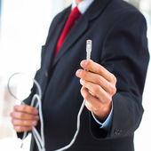 Businessman holding an ethernet cable — Stock Photo