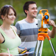 Two young land surveyors at work — Stock Photo #47189743