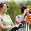 Two young land surveyors at work — Stock Photo #47189759