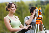Two young land surveyors at work — Stock Photo