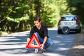 Young man with his car broken down — Stockfoto