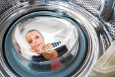 Housework: young woman doing laundry — Stock Photo