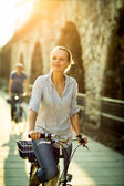 Woman riding a bicycle in a city — Stock Photo