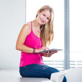 Young female student listening to music — Stock Photo