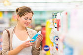 Young woman shopping for cosmetics — Stock Photo