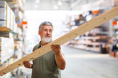 Man choosing and buying construction wood — Stock Photo