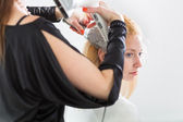 Hairstyle artist working on a young woman's hair — Stock Photo