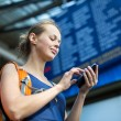 Woman in a train station, sending message — Stock Photo #50021917