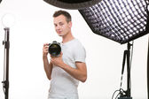 Young pro photographer with digital camera — Stock Photo
