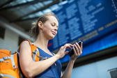 Woman in a train station, sending message — Stock Photo