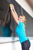 Pretty young college teacher washing the chalkboard — Foto de Stock