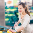 Pretty, young woman shopping for fruits and vegetables — Stock Photo #9388954