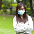 Stock Photo: Womwearing protective face mask in park