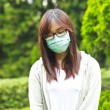 Stock Photo: Woman wearing mask in park