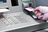 Hand inserting ATM credit card into bank machine to withdraw mon — Stock Photo