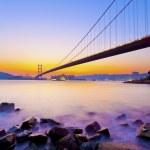 Bridge at coast with sea stones in sunset — Stock Photo #33432685