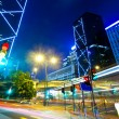 Light trails with modern buildings background — Stock Photo