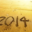 New year 2014 digits on ocean beach sand — Stock Photo #41999461