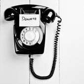 Retro phone with a note to donate to charity — Stock Photo